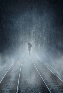 Man with unbrella on rail track in the rainy weather